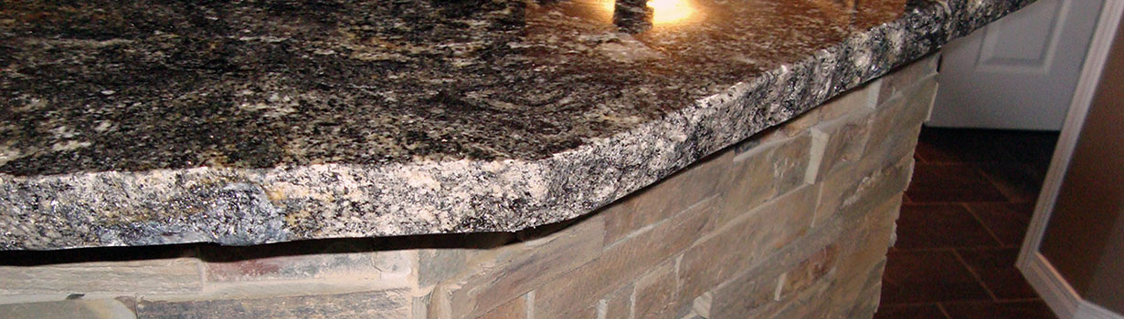 Close up of a dark granite kitchen counter top and stone veneer under it.